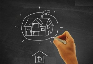 Hand drawing a house on blackboard - Real estate and housing concept